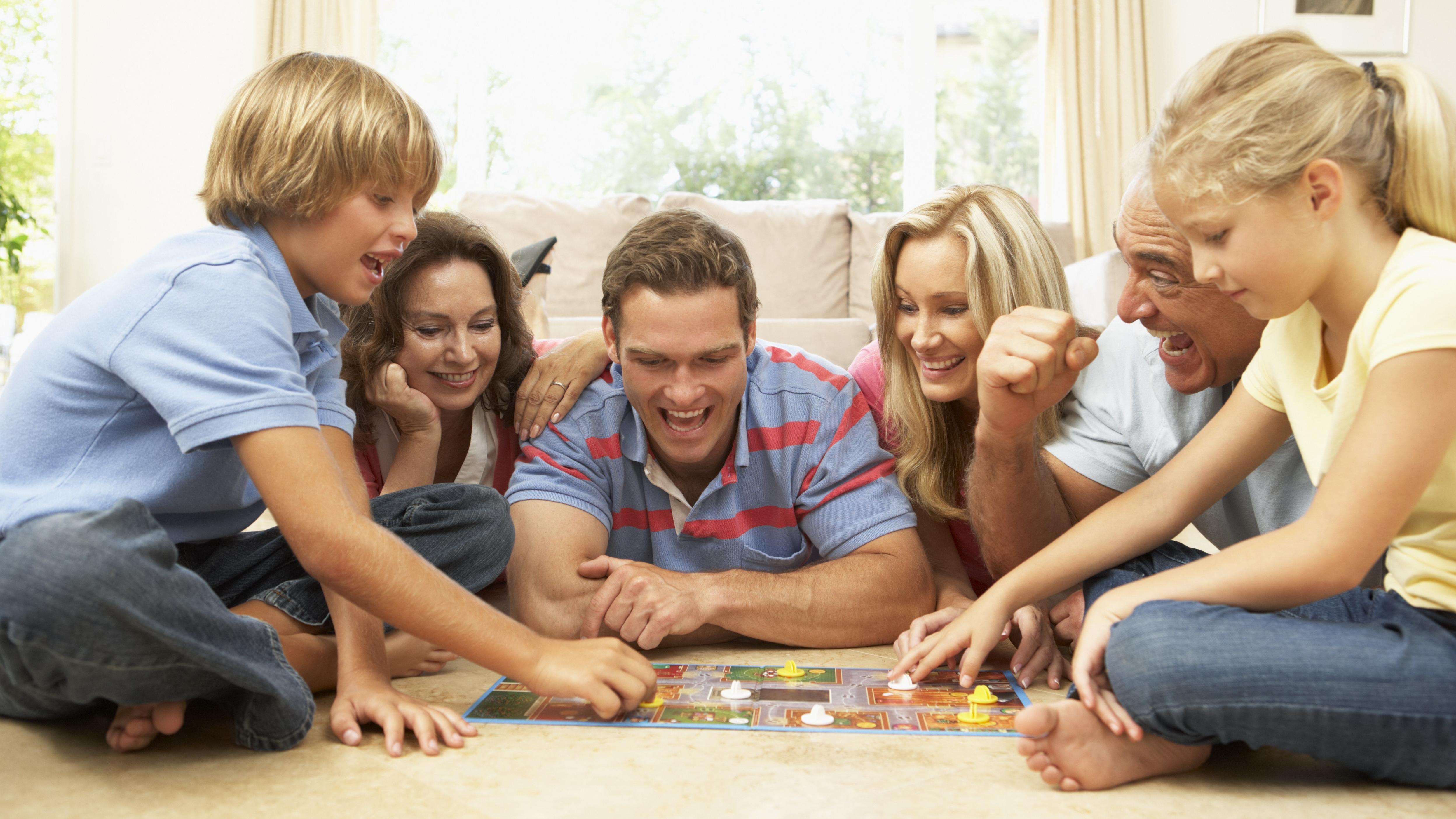 Família jogando jogo de tabuleiro juntos em casa